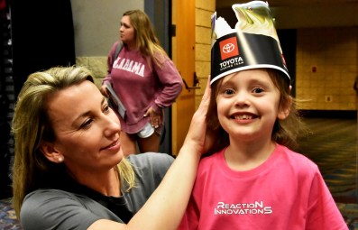 A mother fits her daughter with a fish hat at the Bassmaster Classic Expo at the Birmingham-Jefferson Convention Complex. (Solomon Crenshaw Jr./Alabama NewsCenter)