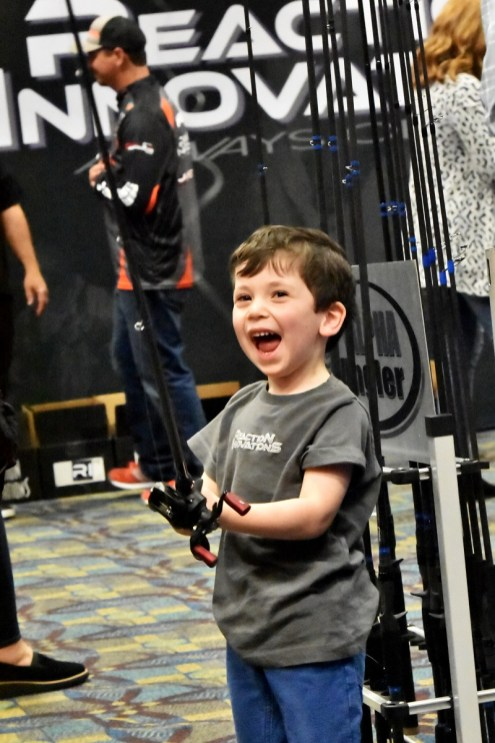 A young fan gets hooked on fishing at the Bassmaster Classic Expo at the Birmingham-Jefferson Convention Complex. (Solomon Crenshaw Jr./Alabama NewsCenter)