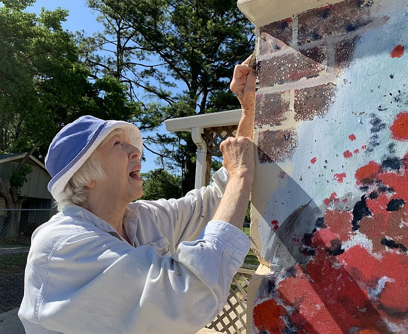Wilson paints bricks at the top of the shelter. (Donna Cope/Alabama NewsCenter)