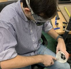 Satterfield smooths the mask's interior surface with a drimel drill. (Donna Cope/Alabama NewsCenter)