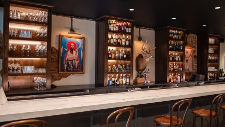 Two colorful paintings by guitarist Browan Lollar of St. Paul and the Broken Bones are behind the stunning stone-topped bar. A handsome trophy deer, from one of Rob's hunting trips, hangs between them. (Dennis Washington / Alabama NewsCenter)