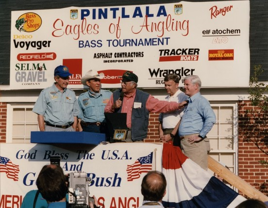 James Martin, center, leads the proceedings at the Pintlala Eagles of Angling Bass Tournament, where the guests included President George H.W. Bush, left. (contributed)