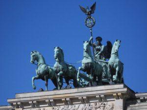 La Cuadriga, creada por Johann Gottfried Schadow, representa a la diosa de la paz Irene montada en un carro tirado por cuatro caballos en dirección a la ciudad.