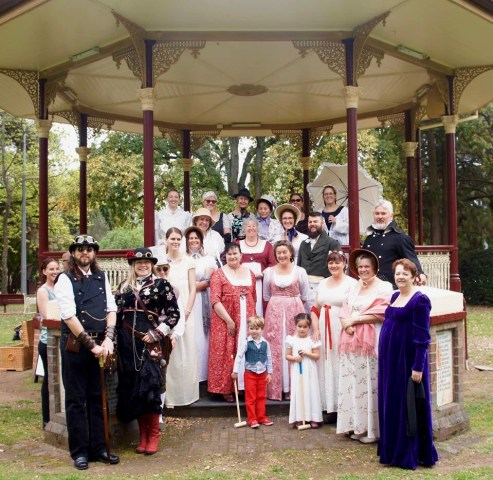 A group of people in historical and steam punk costume on the steps of a rotunda in a park.