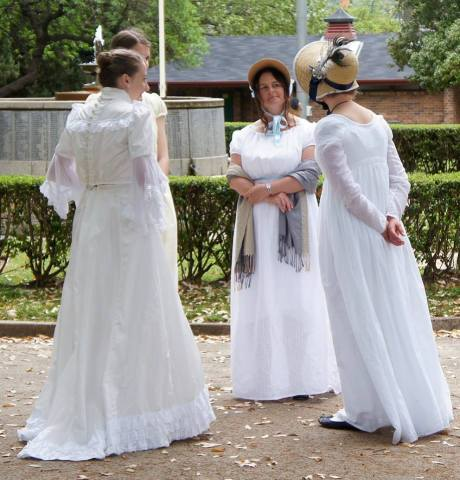 Three ladies in Jane Austen and Victorian costume chatting in a park.