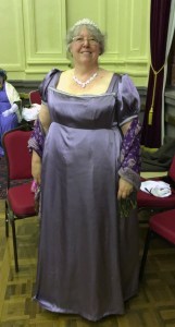 Bron in mauve satin gown with purple shawl and tiara