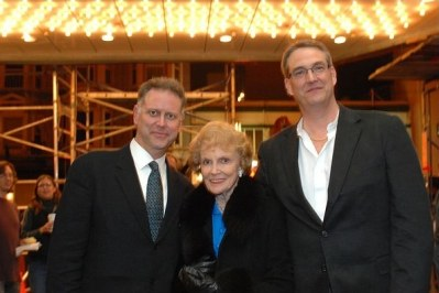 photo of Eddie Muller, Joan Leslie, and Alan K. Rode beneath glowing marquee lights