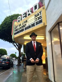 photo of Alan K. Rode standing beneath Aero Theater marquis for the John Brahm Tribute