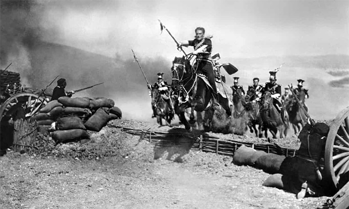 film still showing horseback-riding errol flynn charging a battlement jumping his horse over barrier
