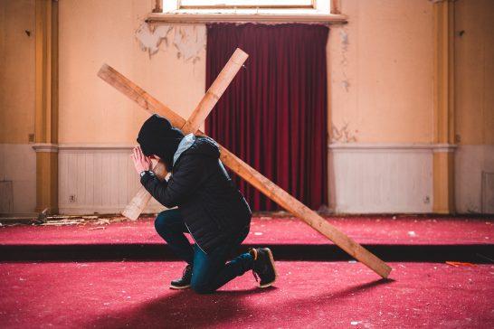 Man kneeling with Cross over shoulder