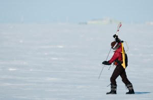 UW graduate student Melinda Webster uses a probe to measure snow depth and verify NASA airborne data. She is walking on sea ice near Barrow, Alaska in March 2012. Her backpack holds electronics that power the probe and record the data. Image-Chris Linder / Univ. of Washington