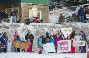 Residents of the village of Nanwalek, Alaska, greet Guardsmen from the Alaska Army National Guard who delivered presents in a CH-47 Chinook helicopter from 1st Battalion, 207th Aviation Regiment, during Operation Santa, Dec. 11. Operation Santa Claus. (U.S. Army National Guard photo by Edward Eagerton/Released)