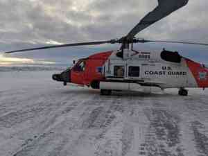 A Coast Guard Air Station Kodiak MH-60 Jayhawk helicopter crew sits on the ground in Nome after recovering two stranded hunters from the Punuk Islands, near St. Lawrence Island. U.S. Coast Guard photo by Lt. Daniel Beshoar.