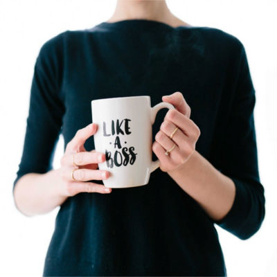 "A person holding a cup that says ""Like a Boss"""