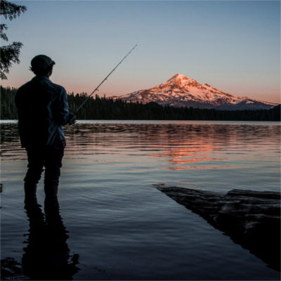 A person fishing by a mountain