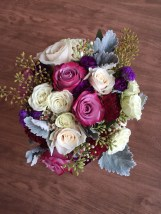 Alaska Winter Wedding | purple roses, plum mini carnations, burgundy carnations, white roses, dusty miller, eucalyptus and wax flower. Bound with white ribbon and a purple corset. Designed by Natasha Price of Alaskaknitnat.com