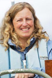Woman smiling, steering boat