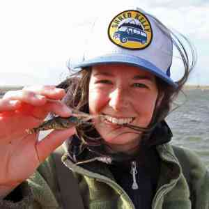 Young woman with 'Shred Kelly' hat and green jacket holding up a very small fish