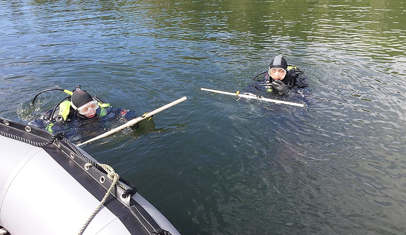 Lauren Bell and Taylor White swim transect lines back to their boat after using them to count and measure abalone.