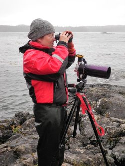 Ginny Eckert on shore with spotting scope and binoculars