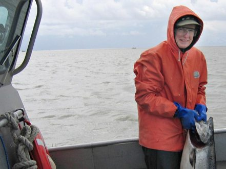 Woman in orange fishing jacket holding large salmon