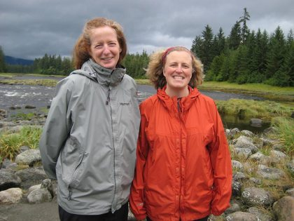 Two smiling woman standing near a river