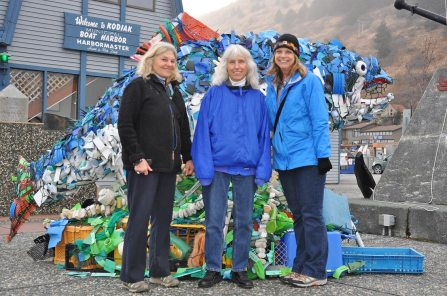 Three woman standing in front of a large salmon sculpture made of marine debris