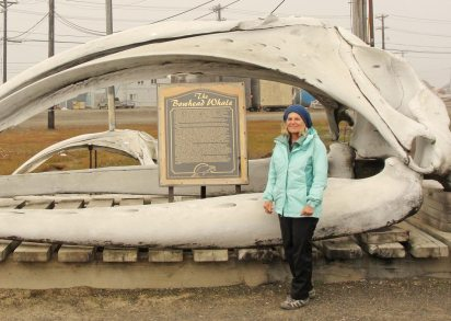 woman in green jacket standing in front of a bowhead whale skull