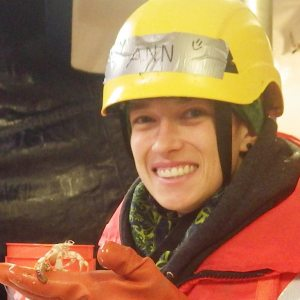 Woman in safety gear, holding small marine creature