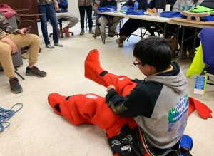 crew class student seated on floor, donning orange survival suit