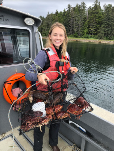 photo of Becca Cates on a boat holding a crab pot