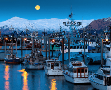 Moon rising over harbor with boats