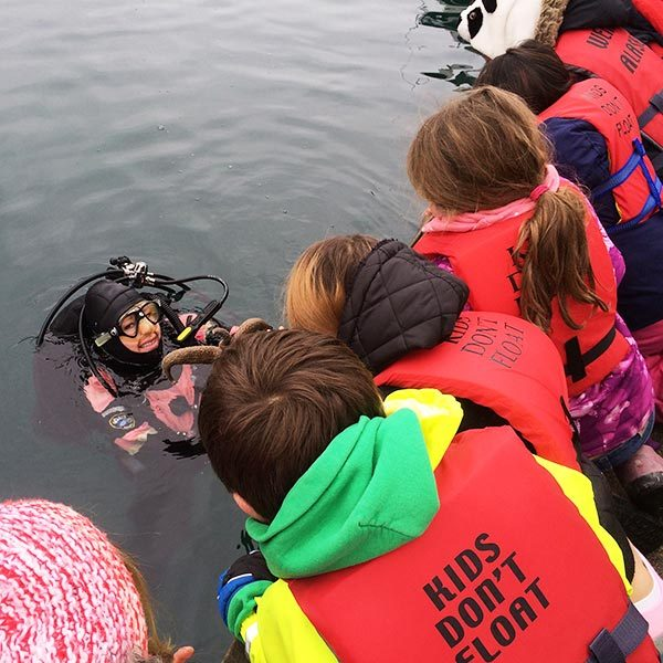 Kids on a dock looking down at SCUBA diver