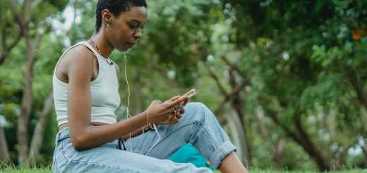 focused black woman with smartphone on lawn