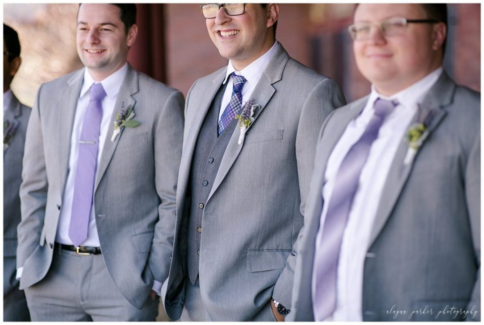 An image of a closeup view of the groom and some of his groomsmen in their gray tuxedos and classy boutonnieres at Station 67 , near the Scioto River by Alayna Parker  - Columbus OH wedding photographer