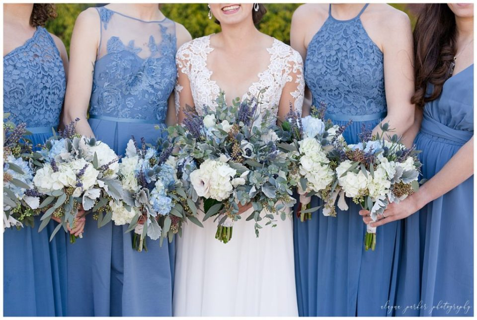 An image of a closeup view of the bride's and bridesmaids' bouquets lined up, showing the beautiful blue and purple flowers at Station 67 , near the Scioto River by Alayna Parker Photography  - Columbus OH wedding photographer