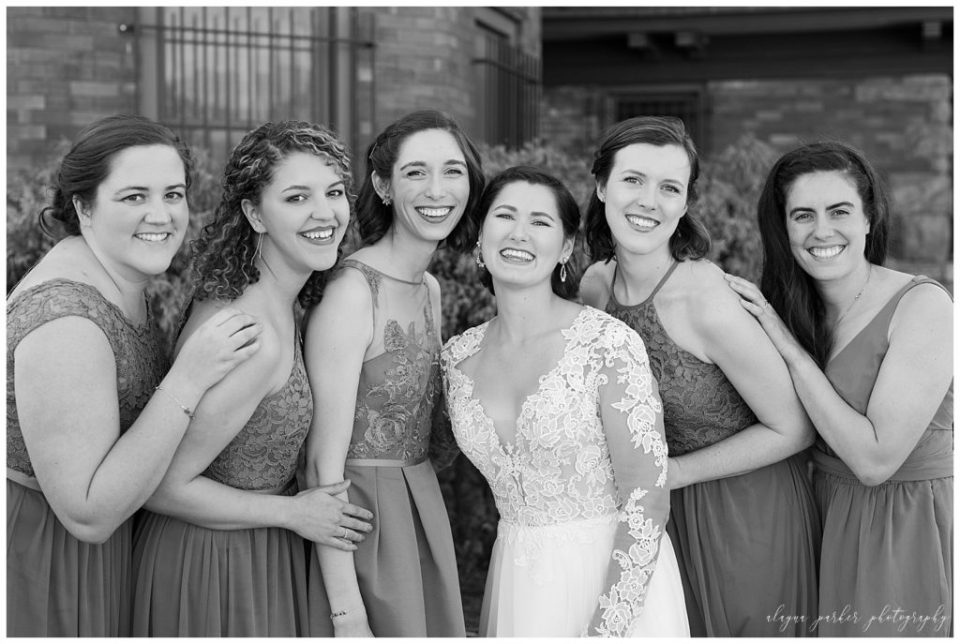 A photograph in black and white of the bride and bridesmaids leaning in together, smiling and relaxing together at Station 67 on W Broad St in Columbus by Alayna Parker  - Columbus OH wedding photography