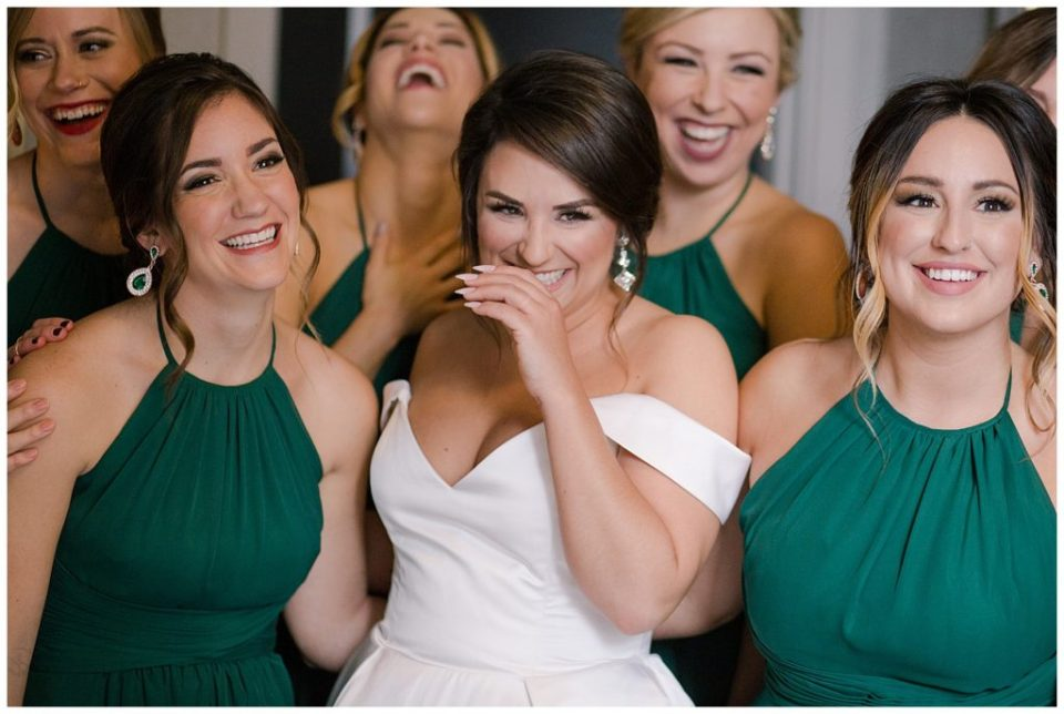A picture of a bride laughing with her bridesmaids as they relax before the wedding at the Hotel LeVeque in Downtown Columbus by Alayna Parker  - Columbus  wedding images