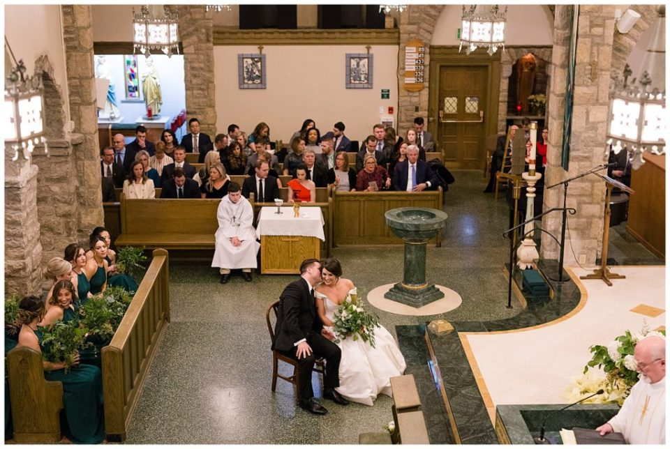 A picture of the bride and groom whispering together, sitting near the church stage as they wait for the wedding ceremony to start by Alayna Parker Photography  - Columbus  wedding photographer