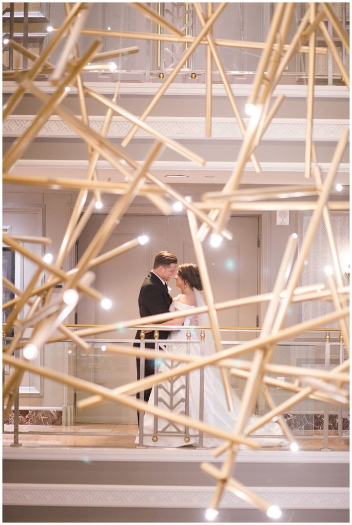 A photograph of the bride and groom romantically holding each other as they are viewed from afar through a dramatic modern lighting fixture at the Hotel LeVeque by Alayna Parker Photography  - Columbus OH wedding photographer