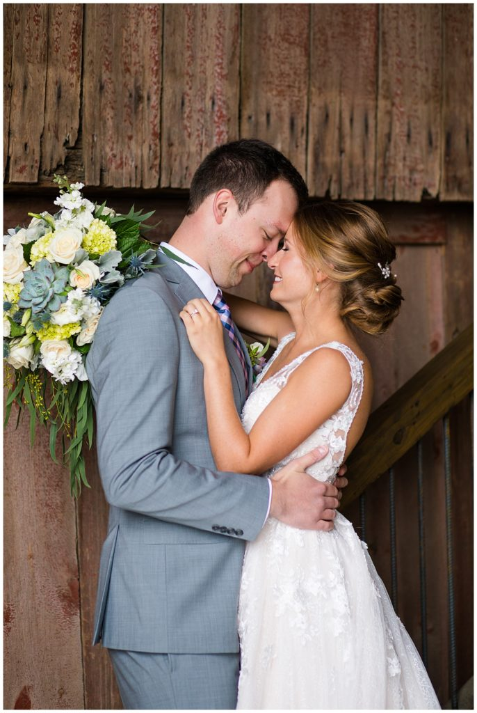 A photograph of a bride and groom holding each other close, touching foreheads and smiling tenderly at a Buckeye Barn wedding by Alayna Parker  - Columbus OH marriage photographer