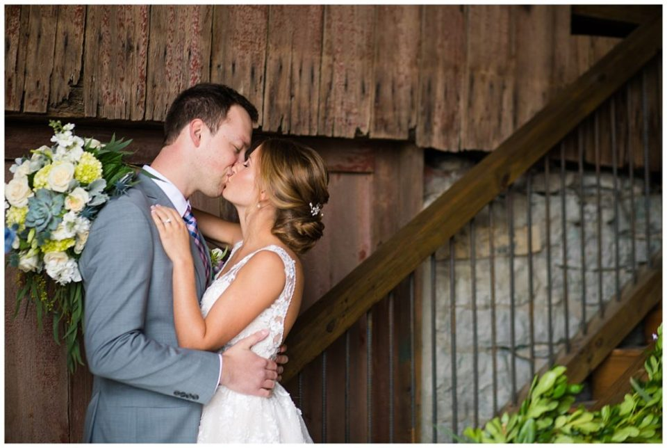A picture of a bride and groom kissing romantically with a rustic barn background at the Buckeye Barn wedding venue by Alayna Parker Photography  - Columbus  wedding photographer
