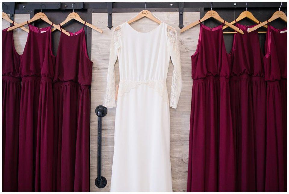 long sleeve wedding dress hanging with burgundy bridesmaids dresses