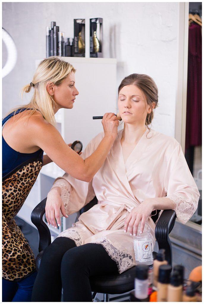 bride getting makeup done at salon