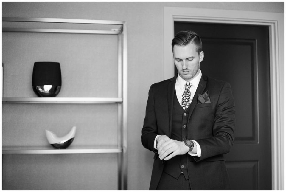 black and white image of groom putting on watch