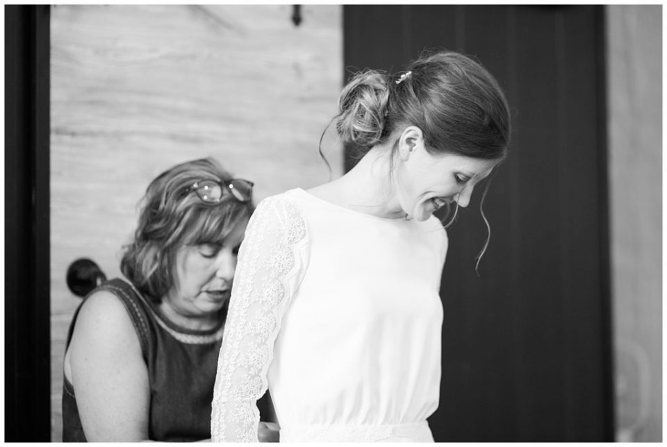 black and white image of mother helping bride into wedding dress