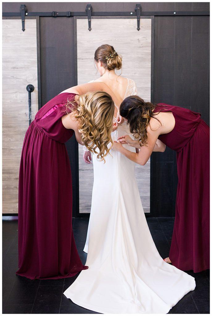 two bridesmaids helping bride get into wedding dress