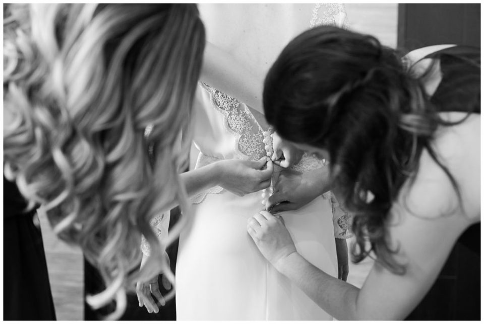 black and white image of bride getting wedding dress buttoned