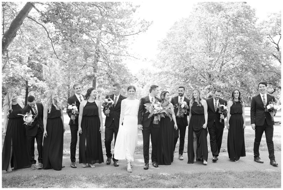 black and white image of bridal party laughing and walking