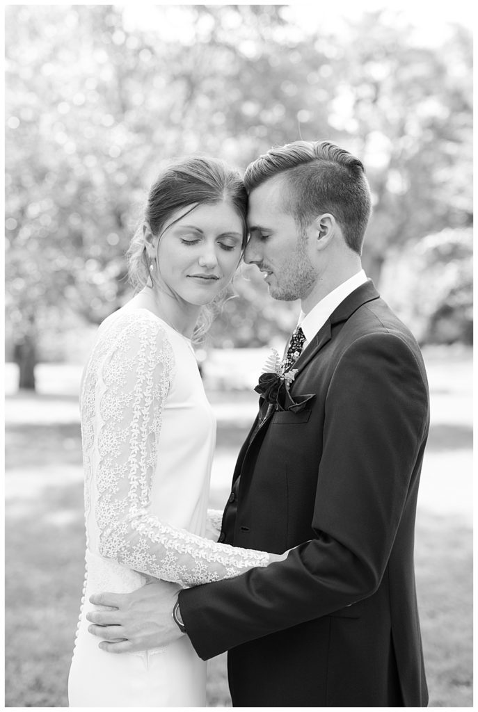 An image in black and white of a bride and groom holding each other, pausing in a tender moment at Dock 580 wedding venue in downtown Columbus by Alayna Parker Photography  - Columbus Ohio marriage photography